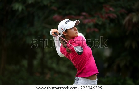 KUALA LUMPUR, MALAYSIA - OCTOBER 11, 2014: Azahara Munoz of Spain tees off at the fourth hole of the KL Golf & Country Club during the 2014 Sime Darby LPGA Malaysia golf tournament. - stock photo