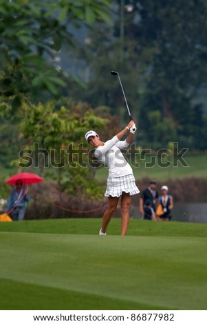 KUALA LUMPUR, MALAYSIA - OCTOBER 16: Azahara Munoz of Spain watches her shot from the fairway of the KL Golf & Country Club at the Sime Darby LPGA 2011 on October 16, 2011 in Kuala Lumpur, Malaysia. - stock photo