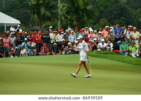KUALA LUMPUR, MALAYSIA - OCTOBER 16: Azahara Munoz of Spains prepares for her putt on day 4 of the Sime Darby LPGA Malaysia 2011 golf tournament on Oct 16, 2011 in Kuala Lumpur, Malaysia. - stock photo