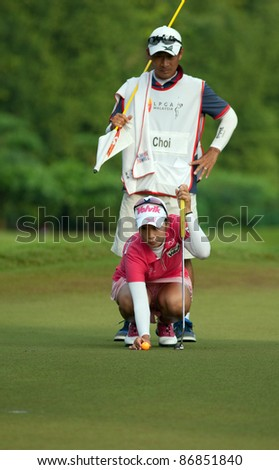 KUALA LUMPUR, MALAYSIA - OCTOBER 16: Chella Choi of South Korea lines up for her putt at the Sime Darby LPGA Malaysia 2011 in Kuala Lumpur Golf & Country Club, Malaysia on October 16, 2011. - stock photo
