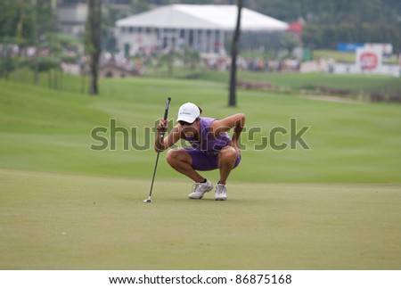 KUALA LUMPUR, MALAYSIA - OCTOBER 16: Dewi Claire Schreefel of the Netherlands lines up for a putt at the Sime Darby LPGA Malaysia on October 16, 2011 at the Kuala Lumpur Golf & Country Club, Malaysia. - stock photo