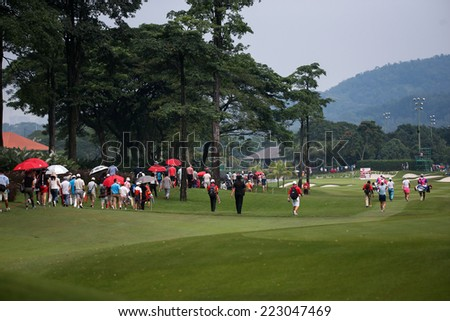 KUALA LUMPUR, MALAYSIA - OCTOBER 11, 2014: Golf fans and locals follow the leaders' flight at the fourth hole of the KL Golf & Country Club during the 2014 Sime Darby LPGA Malaysia golf tournament. - stock photo