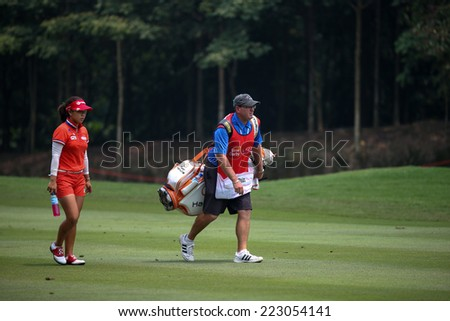 KUALA LUMPUR, MALAYSIA - OCTOBER 10, 2014: Jenny Shin of the USA walks on the fairway of the ninth hole of the KL Golf & Country Club at the 2014 Sime Darby LPGA Malaysia golf tournament. - stock photo