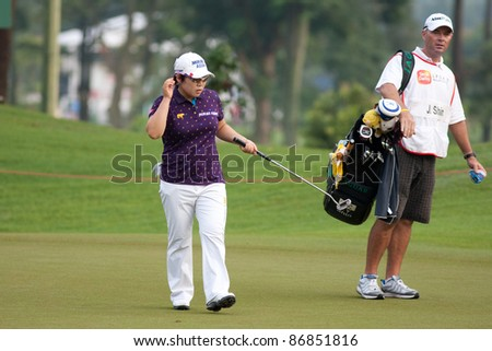 KUALA LUMPUR, MALAYSIA - OCTOBER 16: Jiyai Shin of South Korea prepares for her next shot during the Sime Darby LPGA Malaysia 2011 in Kuala Lumpur Golf & Country Club, Malaysia on October 16, 2011. - stock photo