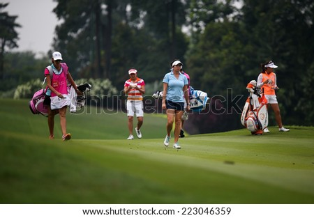 KUALA LUMPUR, MALAYSIA - OCTOBER 11, 2014: LPGA golfers walk on the fairway of the third hole of the KL Golf & Country Club during the 2014 Sime Darby LPGA Malaysia golf tournament. - stock photo