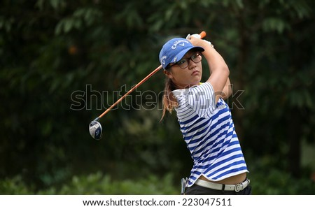 KUALA LUMPUR, MALAYSIA - OCTOBER 11, 2014: Lydia Ko of New Zealand tees off at the fourth hole of the KL Golf & Country Club during the 2014 Sime Darby LPGA Malaysia golf tournament. - stock photo