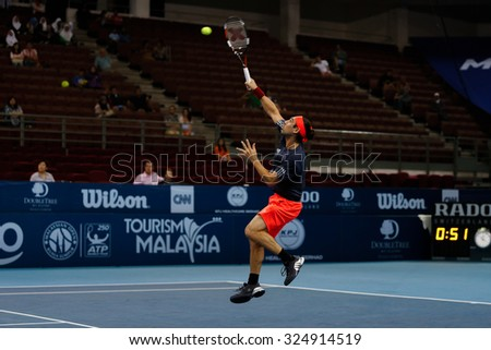 KUALA LUMPUR, MALAYSIA - OCTOBER 01, 2015: Marcos Baghdatis of Cyprus plays a smash return during his match at the Malaysian Open 2015 Tennis tournament held at the Putra Stadium, Malaysia. - stock photo