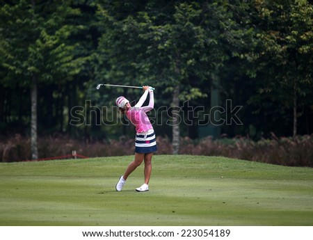KUALA LUMPUR, MALAYSIA - OCTOBER 10, 2014: Mi Hyang Lee of South Korea plays on the fairway of the ninth hole of the KL Golf & Country Club at the 2014 Sime Darby LPGA Malaysia golf tournament. - stock photo