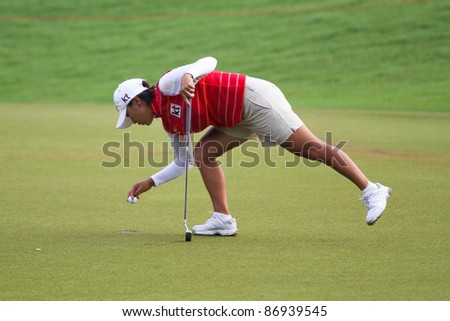 KUALA LUMPUR, MALAYSIA - OCTOBER 16: Mi Hyun Kim of South Korea collects the ball after her putt at the Sime Darby LPGA Malaysia 2011 golf tournament on Oct 16, 2011 in Kuala Lumpur, Malaysia. - stock photo