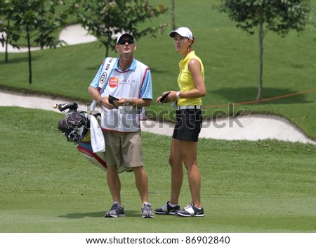 KUALA LUMPUR, MALAYSIA - OCTOBER 16: Michelle Wie of the USA discusses with her caddie on the final day of the Sime Darby LPGA 2011 golf tournament on Oct 16, 2011 in Kuala Lumpur, Malaysia. - stock photo