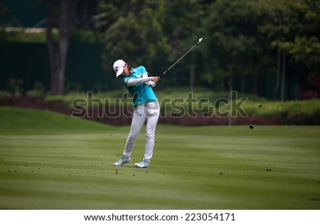 KUALA LUMPUR, MALAYSIA - OCTOBER 10, 2014: Na Yeon Choi of South Korea plays on the fairway of the ninth hole of the KL Golf & Country Club at the 2014 Sime Darby LPGA Malaysia golf tournament. - stock photo