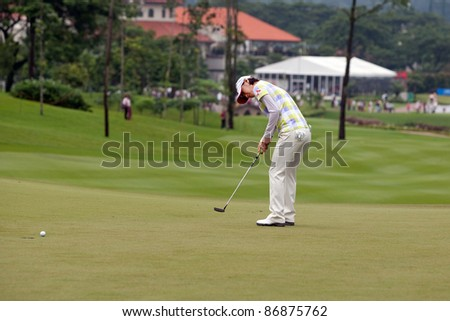 KUALA LUMPUR, MALAYSIA - OCTOBER 16:Na Yeon Choi of South Korea putts on the final day of the Sime Darby LPGA Malaysia 2011 on October 16, 2011 at the Kuala Lumpur Golf & Country Club, Malaysia. - stock photo