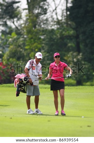 KUALA LUMPUR, MALAYSIA - OCTOBER 16: Paula Creamer discusses with her caddie on hole #9 on day 4 of the Sime Darby LPGA Malaysia 2011 golf tournament on Oct 16, 2011 in Kuala Lumpur, Malaysia. - stock photo