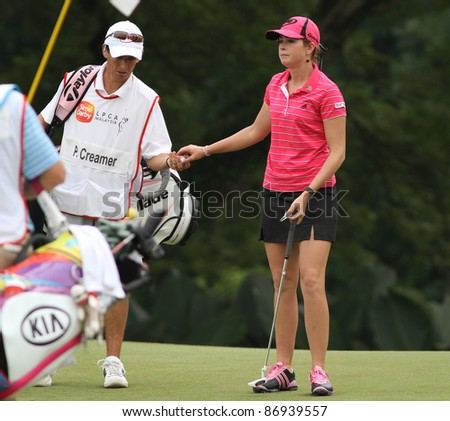 KUALA LUMPUR, MALAYSIA - OCTOBER 16: Paula Creamer of the USA takes the ball from her caddie on day 4 of the Sime Darby LPGA Malaysia 2011 golf tournament on Oct 16, 2011 in Kuala Lumpur, Malaysia. - stock photo