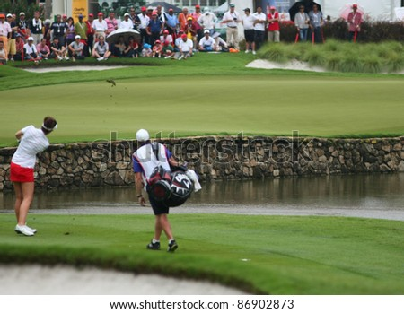 KUALA LUMPUR, MALAYSIA - OCTOBER 16: Sandra Gal of Germany hits towards the green of hole #18 on the final day of the Sime Darby LPGA 2011 golf tournament on Oct 16, 2011 in Kuala Lumpur, Malaysia. - stock photo
