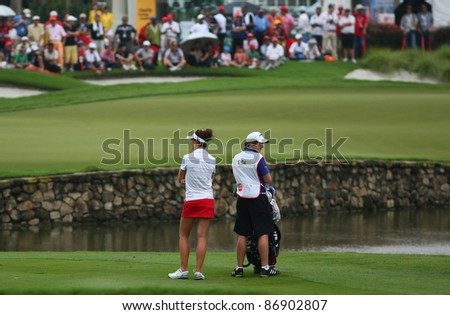 KUALA LUMPUR, MALAYSIA - OCTOBER 16: Sandra Gal of Germany waits for her turn on the fairway of hole #18 during the Sime Darby LPGA 2011 golf tournament on Oct 16, 2011 in Kuala Lumpur, Malaysia. - stock photo