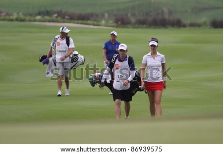 KUALA LUMPUR, MALAYSIA - OCTOBER 16: Sandra Gal of Germany walks with her caddie on the fairway at the Sime Darby LPGA Malaysia 2011 golf tournament on Oct 16, 2011 in Kuala Lumpur, Malaysia. - stock photo