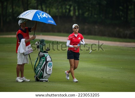 KUALA LUMPUR, MALAYSIA - OCTOBER 10, 2014: So Yeon Rhu of South Korea takes a break at the fairway of the ninth hole of the KL Golf & Country Club at the 2014 Sime Darby LPGA Malaysia golf tournament. - stock photo
