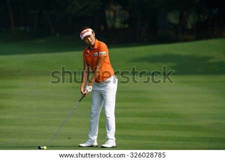 KUALA LUMPUR, MALAYSIA - OCTOBER 09, 2015: South Korea's Il Hee Lee plays from the fairway of the 6th hole of the Kuala Lumpur Golf & Country Club at the 2015 Sime Darby LPGA Malaysia golf tournament. - stock photo
