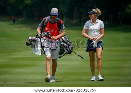 KUALA LUMPUR, MALAYSIA - OCTOBER 09, 2015: USA's Ryan O'Toole discusses with her caddy on the sixth hole fairway of the KL Golf & Country Club at the 2015 Sime Darby LPGA Malaysia golf tournament. - stock photo
