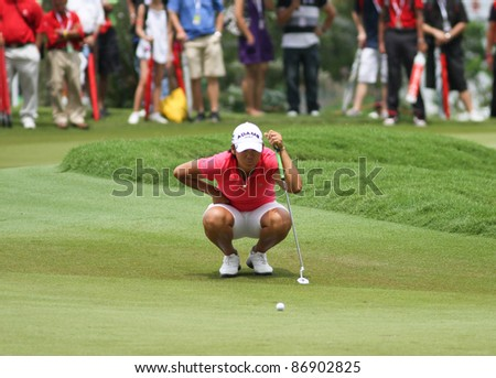 KUALA LUMPUR, MALAYSIA - OCTOBER 16: Yani Tseng of Chinese Taipei lines up a putt at the green of hole #18 during the Sime Darby LPGA 2011 golf tournament on Oct 16, 2011 in Kuala Lumpur, Malaysia. - stock photo