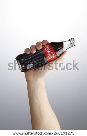 Kuala Lumpur,Malaysia 9th April 2015,Photo of a hand holding glass bottle of Coca Cola - Refreshing. Wet with water ice droplets - stock photo