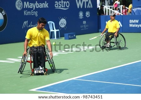 KUALA LUMPUR - MARCH 4: Malaysia Olympic Wheelchair players Abu Samah Borhan (left) & Che Abu Bakar Mat during an exhibition match at the BMW Malaysian Open on March 4, 2012 in Kuala Lumpur, Malaysia