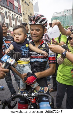 KUALA LUMPUR - MARCH 15 : Mohd Zamri Sale(MAS) rider Terengganu Cycling Team interviewed while carrying his child during stage 8 Le Tour de Langkawi 2015 at Kuala Lumpur, Malaysia on March 15, 2015. - stock photo
