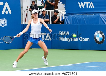 KUALA LUMPUR-MARCH 4: Petra Martic (CRO) returns ball during BMW Malaysia Open against Jelena Jankovic (SRB) on March 4, 2012 in Kuala Lumpur, Malaysia. Martic Won 6:7(5), 7:5, 7:6(5) - stock photo