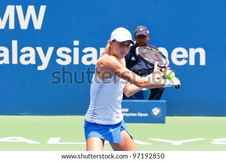 KUALA LUMPUR-MARCH 4:Petra Martic (CRO) returns the ball while compete against Jelena Jankovic (SRB) during BMW Malaysia Open on March 4, 2012 in Kuala Lumpur, Malaysia. Martic Won 6:7(5), 7:5, 7:6(5) - stock photo