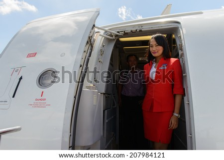 KUALA-LUMPUR - MAY 06: Airasia crew member on May 06, 2014 in Kuala-Lumpur, Malaysia. AirAsia Berhad is a Malaysian low-cost airline headquartered in Kuala Lumpur, Malaysia - stock photo