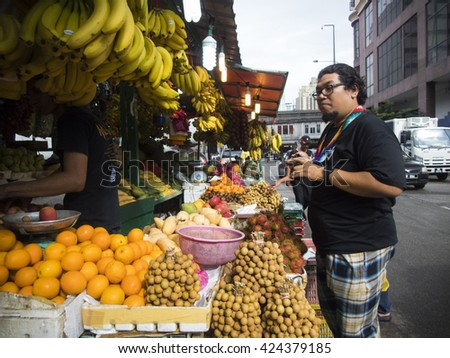 KUALA LUMPUR - MAY 21: an unidentified tourist want to buy fruit from a stall on May 21 2016 in Chow Kit Road, KL. Fruits also included in Goods and Services Tax implemented by the government. - stock photo