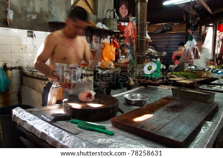 KUALA LUMPUR - MAY 22: Fishmonger in a traditional Chinese wet market works at his stall on May 22, 2011 in Kuala Lumpur, Malaysia. This wet market in Chinatown was started by Chinese immigrants.