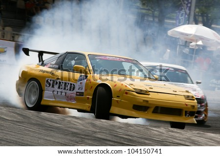 KUALA LUMPUR - MAY 20: Malaysia's Kevin Rajoo (car #23) leaves a trail of smoke as he drifts in this qualifying run during the Formula Drift 2012 Asia Round 1 on May 20, 2012 in Speedcity, Malaysia. - stock photo