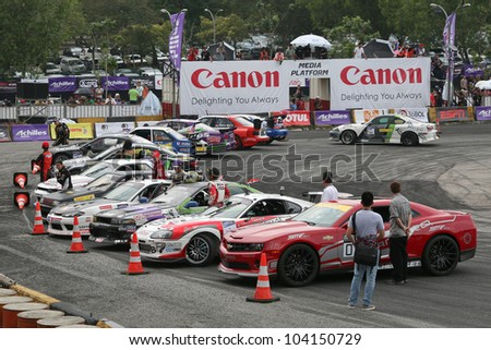 KUALA LUMPUR - MAY 20:The final 16 qualifiers park their competition cars in a parade in front of the grandstand during the Formula Drift 2012 Asia Round 1 on May 20, 2012 in Speedcity, Malaysia.