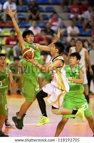 KUALA LUMPUR - OCT 28: Farmcochem's Wee Chuan Chin (white) leaps towards the hoop in a Malaysia National Basketball League match against Crouching Tiger on October 28, 2012 in Kuala Lumpur, Malaysia. - stock photo
