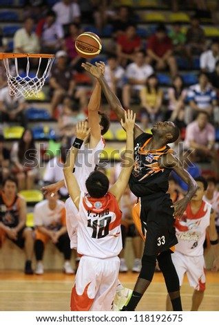 KUALA LUMPUR - OCT 28: Firehorse's players (black) and Dragon's players (white) scramble for a loose ball in a Malaysia National Basketball League match on October 28, 2012 in Kuala Lumpur, Malaysia. - stock photo