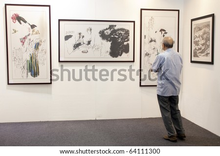 KUALA LUMPUR - OCTOBER 30: A visitor admiring a chinese painting during The Art Expo Malaysia held at the Matrade Exhibition and Convention Centre October 30, 2010 in Kuala Lumpur, Malaysia. - stock photo