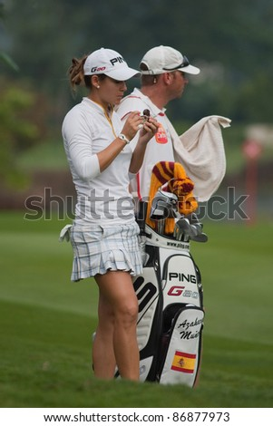 KUALA LUMPUR - OCTOBER 16: Azahara Munoz of Spain snacks in between shots on the fairway of the KL Golf & Country Club at the Sime Darby LPGA 2011 on October 16, 2011 in Kuala Lumpur, Malaysia. - stock photo