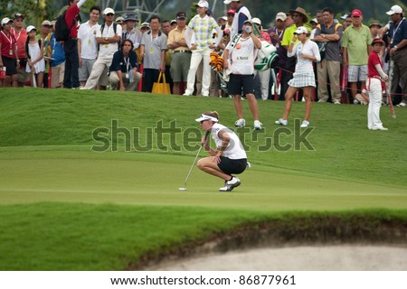 KUALA LUMPUR- OCTOBER 16: Brittany Lang of the USA checks the green of the 18th hole at the KL Golf & Country Club at the Sime Darby LPGA 2011 tournament on October 16, 2011 in Kuala Lumpur, Malaysia. - stock photo