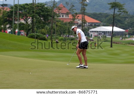 KUALA LUMPUR - OCTOBER 16: Brittany Lang of the USA putts successfully on the final day of the Sime Darby LPGA Malaysia 2011 on October 16, 2011 at the Kuala Lumpur Golf & Country Club, Malaysia. - stock photo