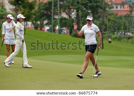 KUALA LUMPUR - OCTOBER 16: Brittany Lang of the USA reacts after her putt on the final day of the Sime Darby LPGA Malaysia 2011 on October 16, 2011 at the Kuala Lumpur Golf & Country Club, Malaysia. - stock photo