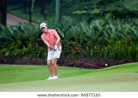 KUALA LUMPUR - OCTOBER 16: Candie Kung of Chinese Taipei watches her shot on the final day of the Sime Darby LPGA Malaysia 2011 on October 16, 2011 at the Kuala Lumpur Golf & Country Club, Malaysia. - stock photo
