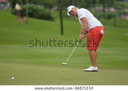 KUALA LUMPUR - OCTOBER 16: Caroline Hedwall of Sweden putts on the final day of the Sime Darby LPGA Malaysia 2011 golf tournament on October 16, 2011 at the Kuala Lumpur Golf & Country Club, Malaysia. - stock photo