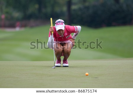 KUALA LUMPUR - OCTOBER 16: Chella Choi of South Korea lines up for a putt on the final day of the Sime Darby LPGA Malaysia 2011 on October 16, 2011 at the Kuala Lumpur Golf & Country Club, Malaysia. - stock photo