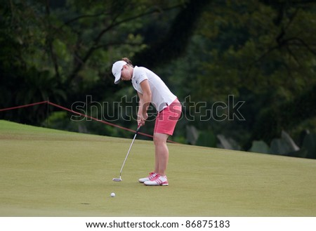 KUALA LUMPUR - OCTOBER 16: Christel Boeljon of the Netherlands putts on the final day of the Sime Darby LPGA Malaysia 2011 on October 16, 2011 at the Kuala Lumpur Golf & Country Club, Malaysia. - stock photo