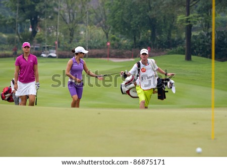 KUALA LUMPUR - OCTOBER 16: Dewi Claire Schreefel of the Netherlands takes the putter from her caddie at the Sime Darby LPGA Malaysia on Oct 16, 2011 at the Kuala Lumpur Golf & Country Club, Malaysia. - stock photo