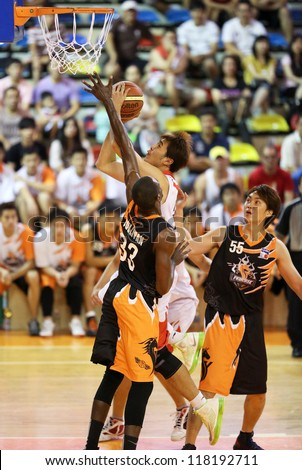 KUALA LUMPUR - OCTOBER 28: Dragons' Chee Li Wei (white) scores against Firehorse's defense (black) in a Malaysia National Basketball League match on October 28, 2012 in Kuala Lumpur, Malaysia. - stock photo