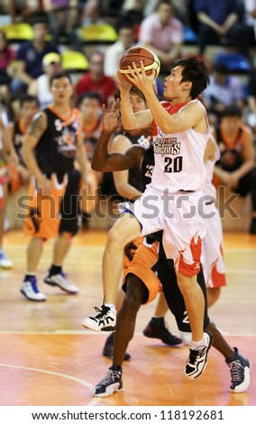 KUALA LUMPUR - OCTOBER 28: Dragons' Loh Shee Fai  #20 scores an easy basket against the Firehorse team in a Malaysia National Basketball League match on October 28, 2012 in Kuala Lumpur, Malaysia. - stock photo
