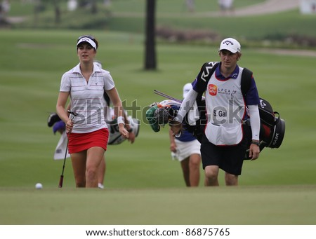 KUALA LUMPUR - OCTOBER 16: Sandra Gal of Germany and her caddies walk on the fairway of the Kuala Lumpur Golf & Country Club at the Sime Darby LPGA 2011 on October 16, 2011 in Kuala Lumpur, Malaysia. - stock photo